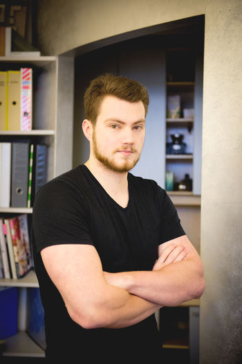 Portrait Of Young Man Standing By Bookshelf At Home