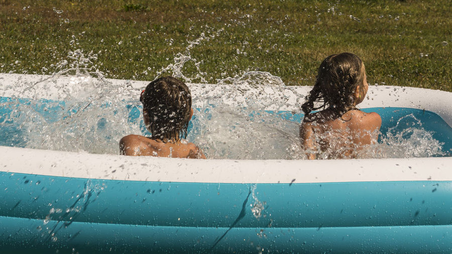 Rear View Of Playful Siblings In Wading Pool At Lawn