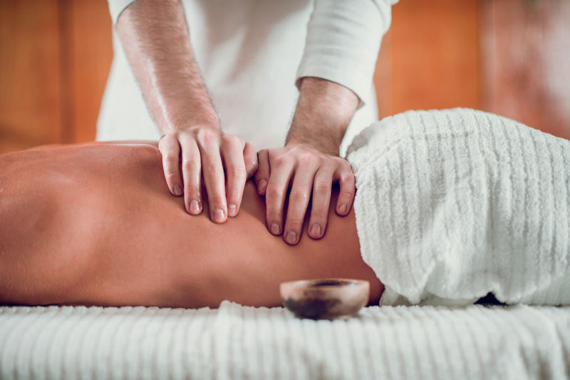 Midsection of male massage therapist massaging shirtless female customer in spa