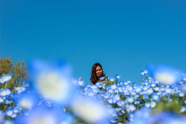 Full length of woman against blue sky