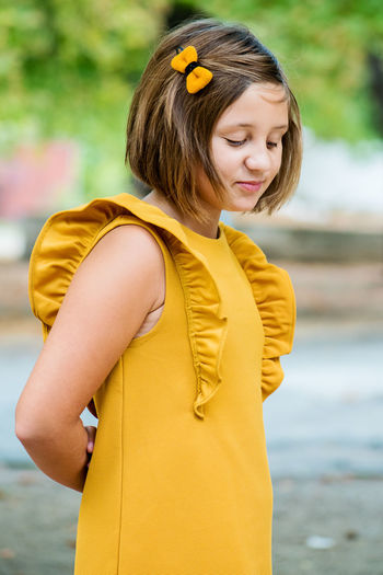 Girl in yellow dress standing on road