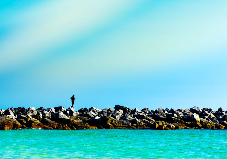 Mid distance view of man standing on rocks at beach