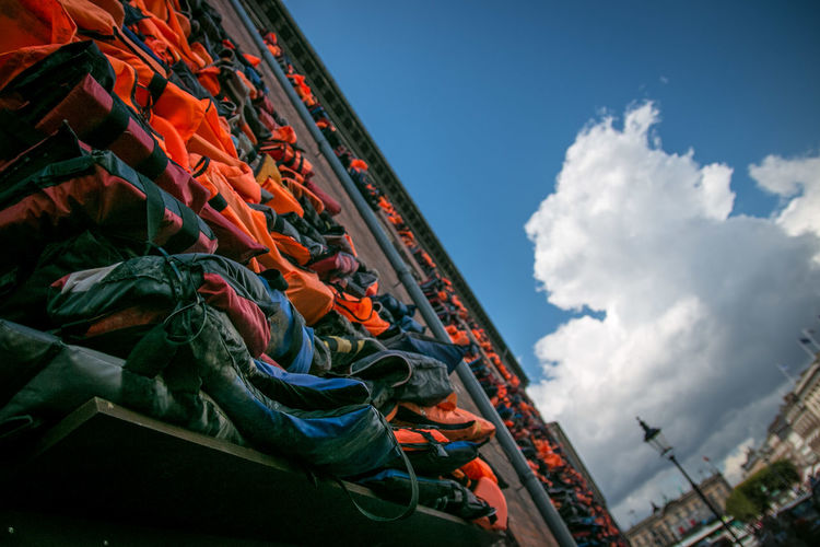 Tilt image of life jackets against cloudy sky in city