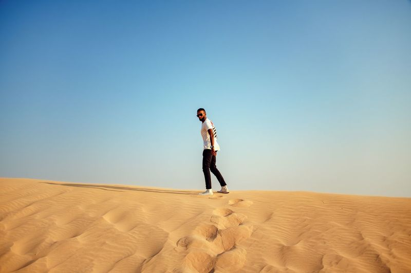 Desert One Person Standing Arid Climate Sand Clear Sky Climate Sand Dune Lifestyles Casual Clothing Man Young Adult A New Perspective On Life