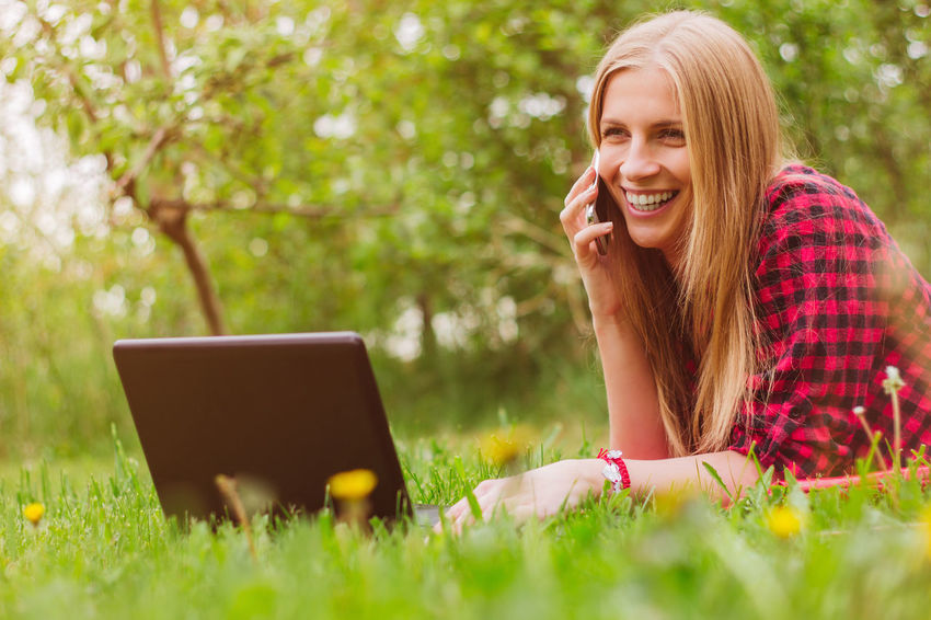 Adult Blond Hair Cheerful Communication Computer Connection Convenience E-mail Enjoyment Grass Happiness Internet Laptop Mobile Phone One Person Portability Smiling Technology Typing Using Laptop Using Phone Wireless Technology Women Working Young Adult