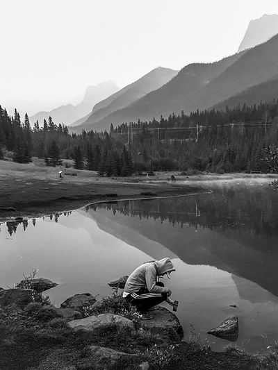 Man Crouching At Lakeshore Against Mountains