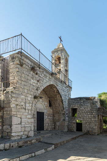 Bar'am, Israel, June 09, 2018 : The fasade with the belfry of the functioning church of the Christian Maronites in the abandoned village Kafr Birim in the north of Israel Christian Maronites Church Cross God Jesus Christ Kafr Birim Abandoned Village Arabic Architecture Art Belfry Tower Bible Building Culture Day Heritage History Holy Israel Landmark Monument Old Pry Religion Symbol