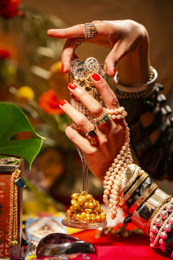 Gestures of a woman with jewelry, pearls, fruits and flowers. Abundance Wealth Celebration Art And Craft Mood Jewelry Gold Pearls Gesture Luxury Human Hand Hand Bracelet Human Body Part Adult Ring One Person Women Bangle Focus On Foreground Close-up Real People Fashion Belief Finger Nail