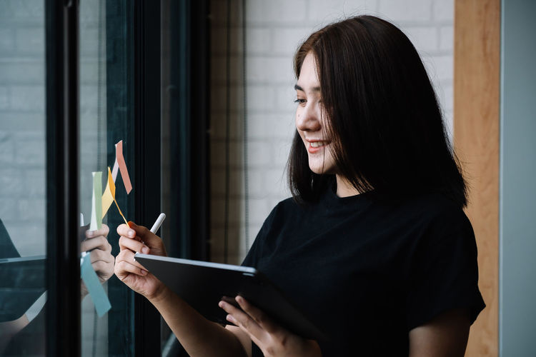 Woman looking at camera while standing against window