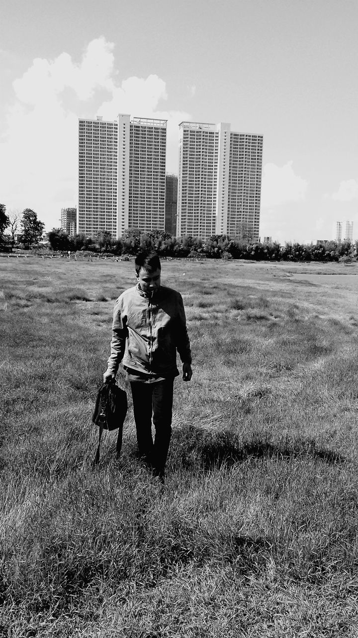 real people, field, full length, walking, one person, grass, architecture, rear view, casual clothing, outdoors, leisure activity, built structure, day, lifestyles, building exterior, standing, sky, men, young adult