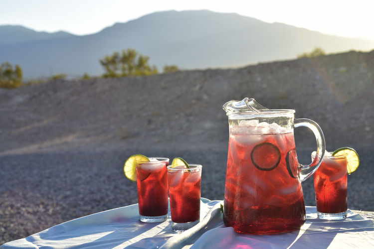 Cold iced tea made from hibiscus flower petal tea in drink glasses and pitcher in hot desert setting