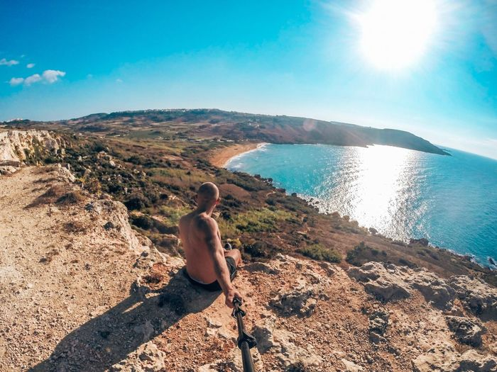 Rear view of man taking selfie sitting on rock by sea against sky
