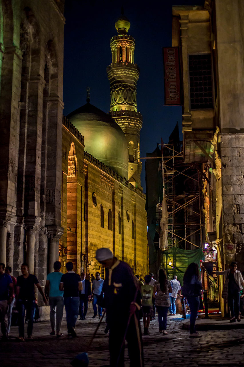 architecture, built structure, building exterior, spirituality, place of worship, religion, real people, night, illuminated, travel destinations, architectural column, men, large group of people, women, outdoors, city, sky, people