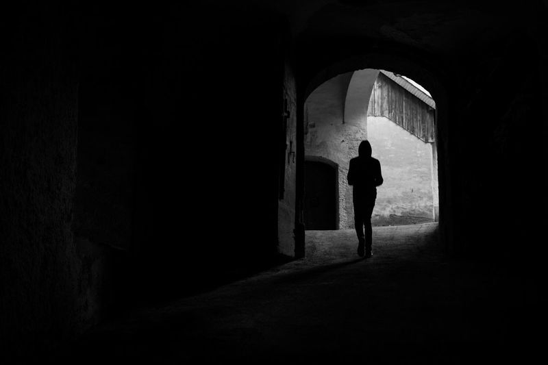 Rear view of silhouette person walking in dark tunnel