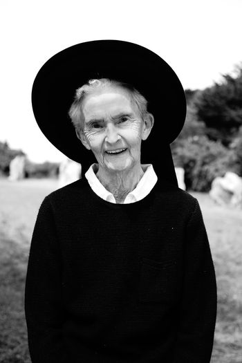 Portrait of smiling old woman standing against hat in traditional costume brittany