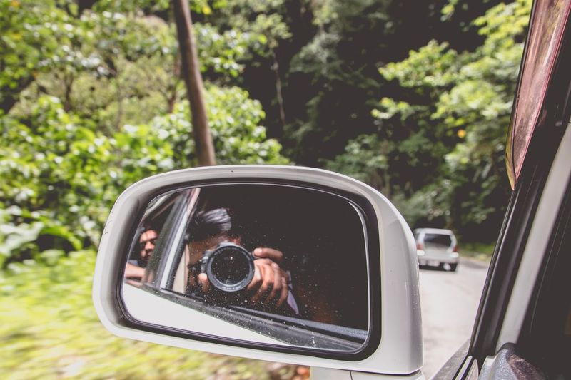 Reflection Of Digital Camera In Side-View Mirror Of Car