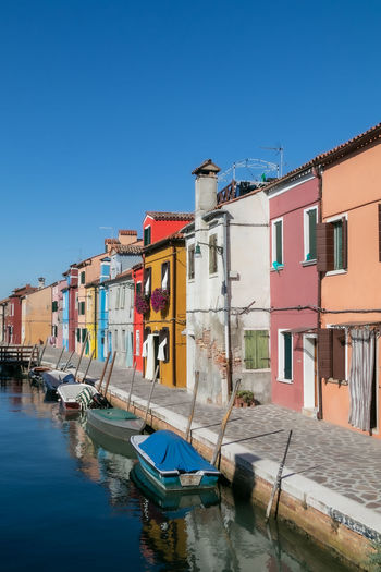 Boats moored in canal by buildings against clear blue sky