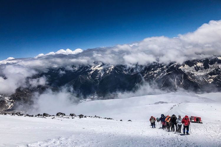 People on snowcapped mountains against sky during winter