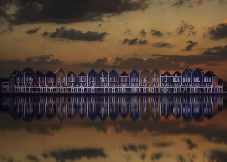 """Dutch architecture in Houten, Holland. The houses are also called """"The Rainbow Houses"""" because of their vibrant colors Architecture Colors EyeEm Best Shots EyeEm Gallery EyeEmBestPics EyeEmNewHere Eyebestedits Home Reflection Sunset_collection Tadaa Community Travel Wooden Houses Clouds And Sky Cosy Dutch Eye4photography  Fall Holland Houten Mirroring In Water No People Still Water Sunset Windows"""