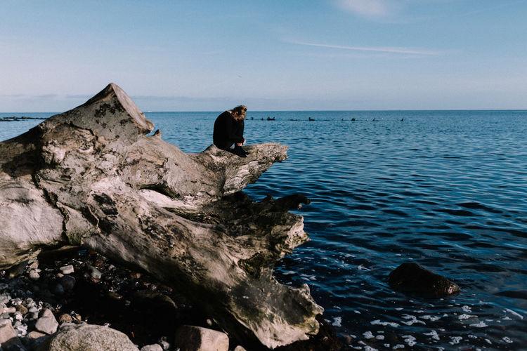 Woman sitting on fallen tree by sea
