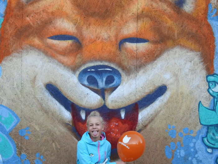 Portrait of girl sticking out tongue against mural wall