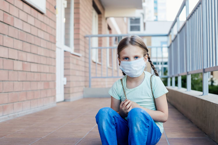 Portrait of girl wearing mask sitting outdoors