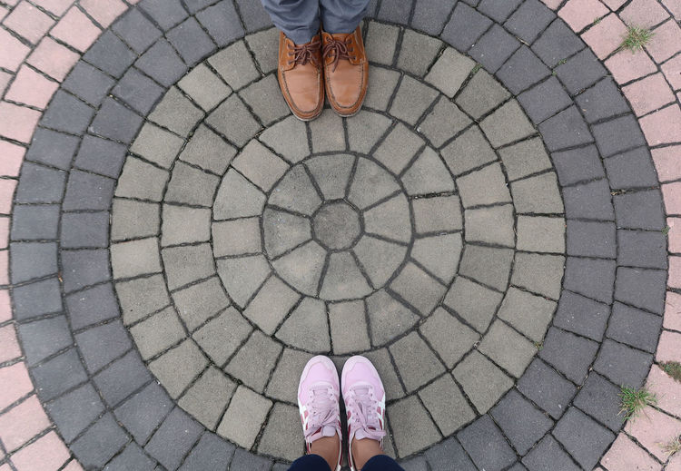 Low section of friends standing on cobblestone