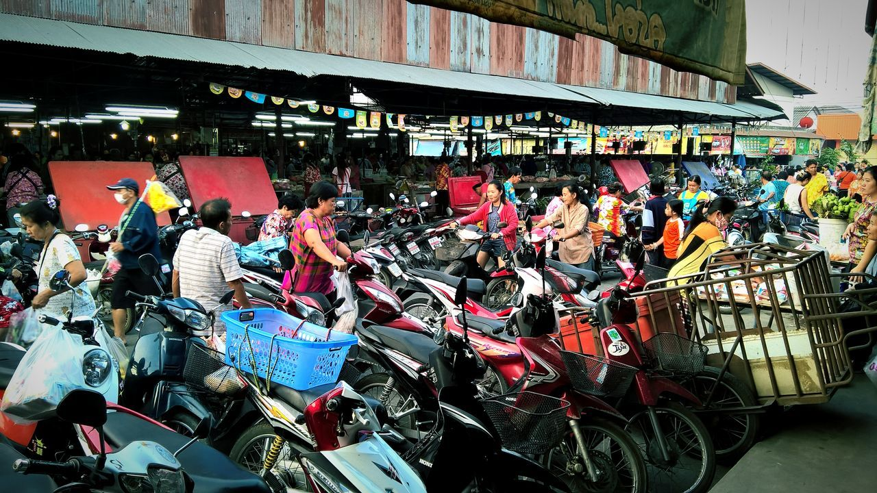 transportation, mode of transport, bicycle, land vehicle, built structure, stationary, large group of people, motorcycle, architecture, real people, day, outdoors, men, city, biker, people