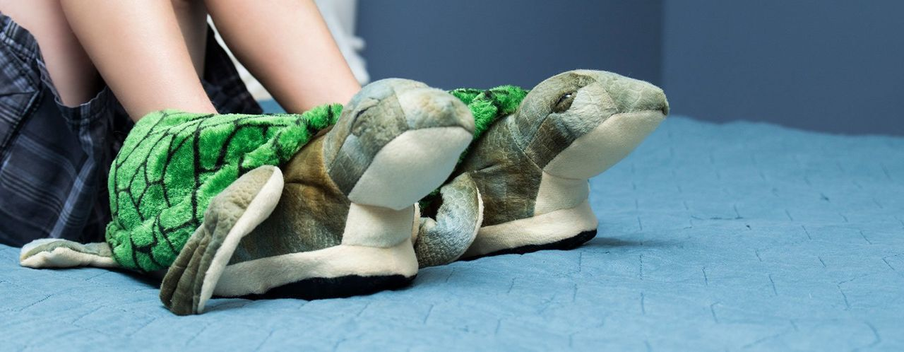 Low section of girl wearing turtle shaped shoes on bed at home