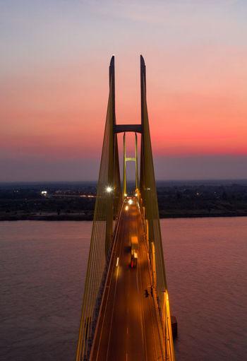Illuminated bridge over sea against sky during sunset