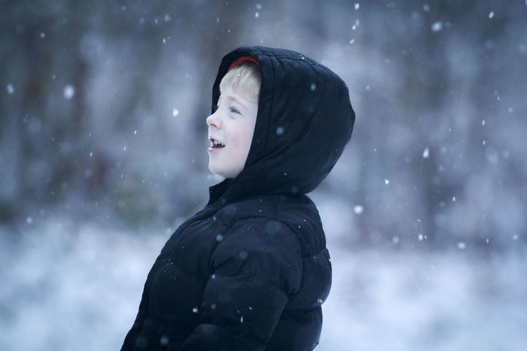 Close-up of boy in warm clothing standing outdoors during snowfall