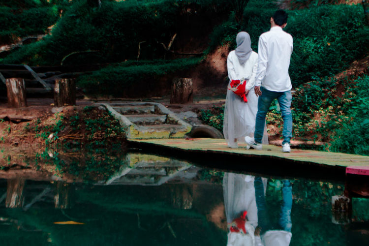 Couple standing by plants in water