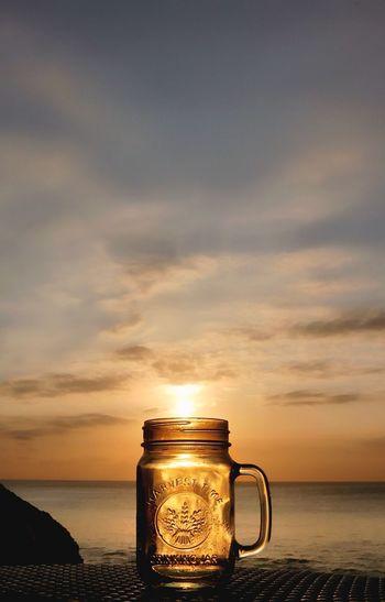 Close-up of illuminated lamp against sea during sunset