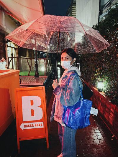 Portrait of woman standing with umbrella in rain