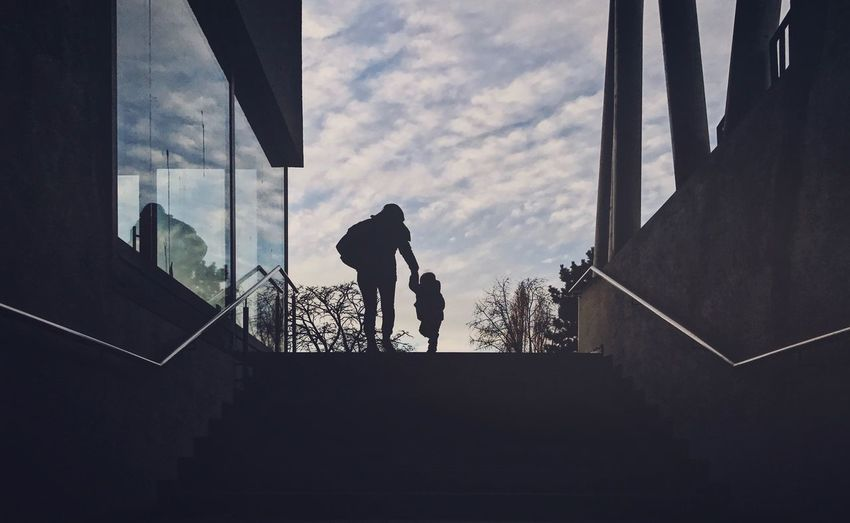 Low angle view of silhouette people walking on staircase