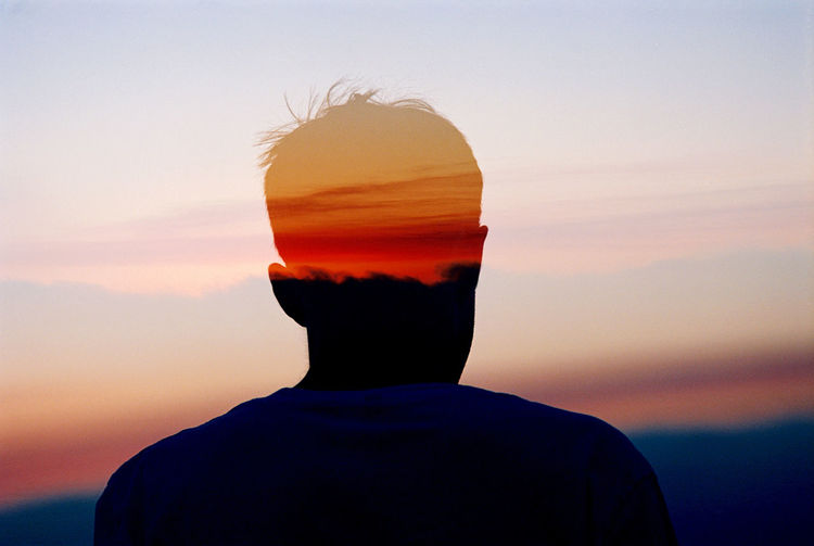 Multiple Exposure Of Man And Orange Sky