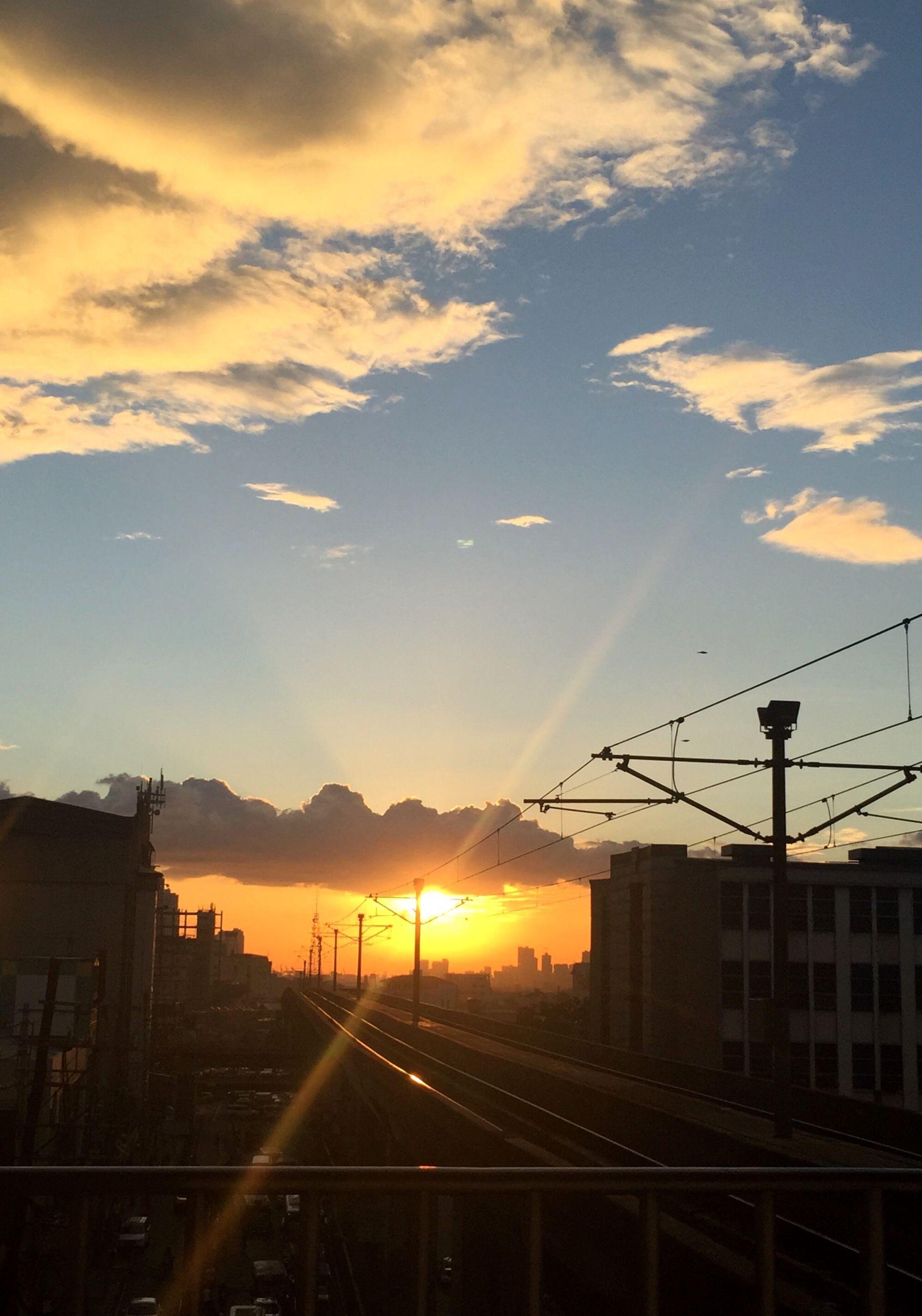 sunset, architecture, built structure, building exterior, orange color, sky, sun, silhouette, city, cloud - sky, sunlight, connection, cloud, outdoors, transportation, railroad track, no people, sunbeam, power line, building