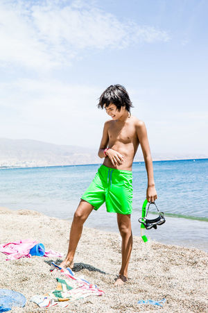 Boy snorkelling at the beach Beach Boys Casual Clothing Childhood Euroasian Full Length Green Trunks Horizon Over Water Landscape Leisure Activity Lifestyles Person Sand Scuba Mask Sea Shore Sky Smiling Snorkeling Standing Summer Sun Tanned Vacations Water Swimwear Vacations Holiday Outdoors One Person