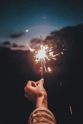 Low angle view of hand holding sparkler at night