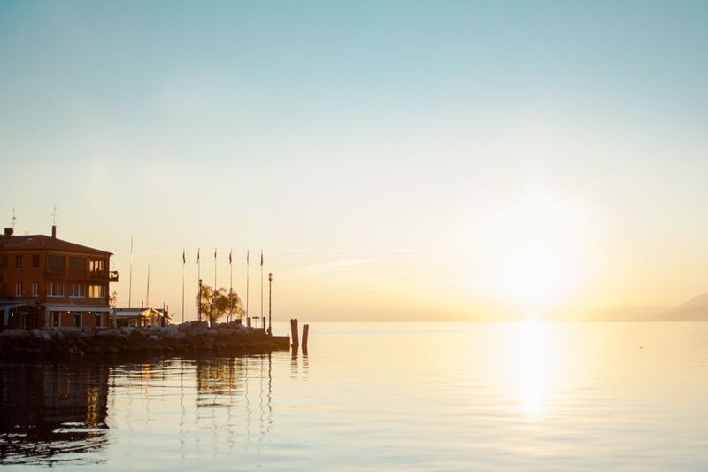 Sunset Water Sea Sky Tranquil Scene Reflection Nature Clear Sky Tranquility Scenics No People Outdoors Beauty In Nature Horizon Over Water Architecture Day Photo Of The Day Sunlight Sun Sunshine Italy Italy Holidays Italy Photos Gardasee Garda