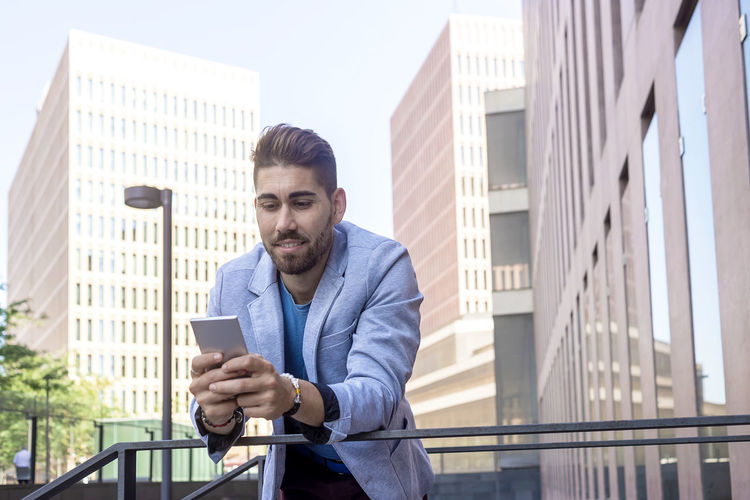 Young man using mobile phone against buildings in city