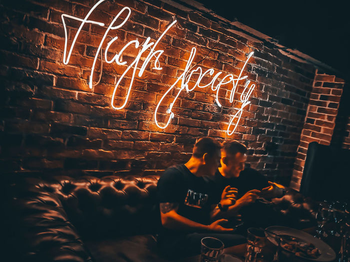 People sitting by illuminated light painting at night
