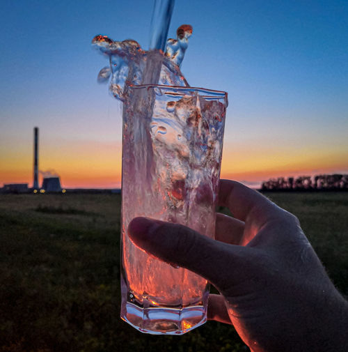Close-up of hand holding drink against sky during sunset