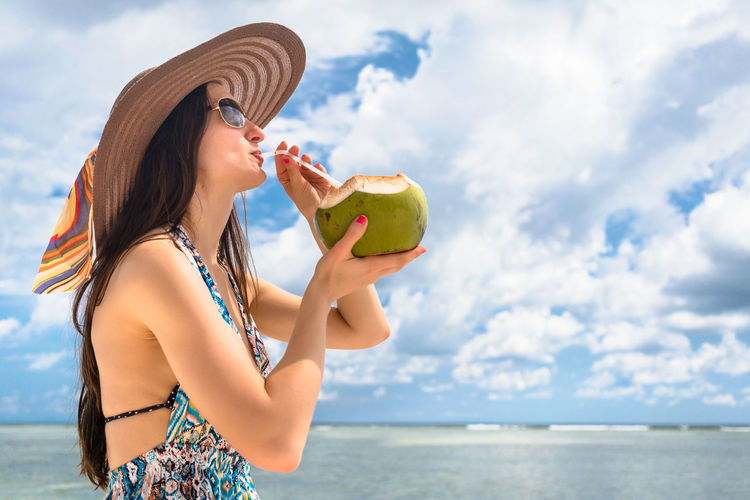 Young woman holding coconut in her tropical vacation