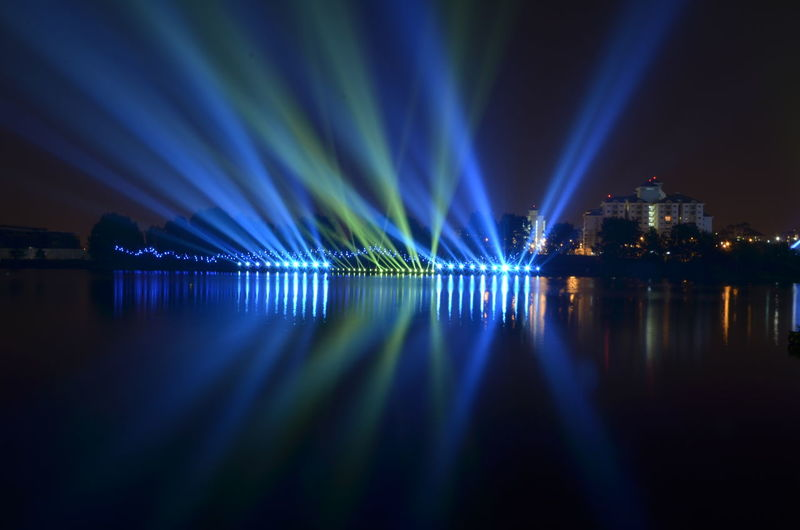 Illuminated lights by river against sky at night