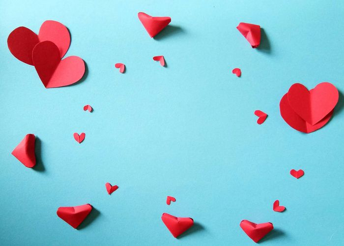 Close-Up Of Heart Shape Papers On Blue Background