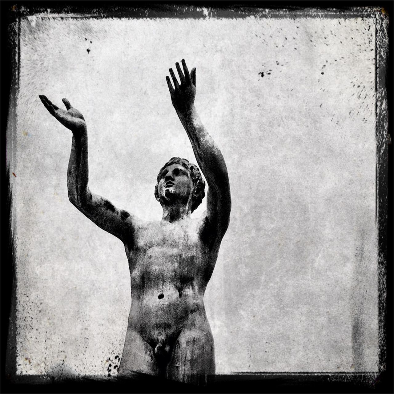 Low angle view of naked male statue against sky