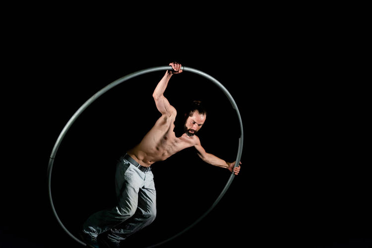 Circus Agility Arms Raised Balance Black Background Effort Elégance Exercising Flexibility Full Length Healthy Lifestyle Human Arm Human Body Part Indoors  One Person Performance Shirtless Skill  Sport Strength Studio Shot Young Adult