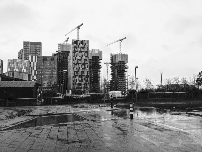 Buildings by wet street against sky in city