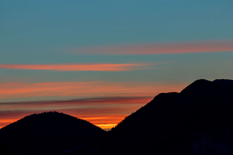 Silhouette mountain against dramatic sky during sunset